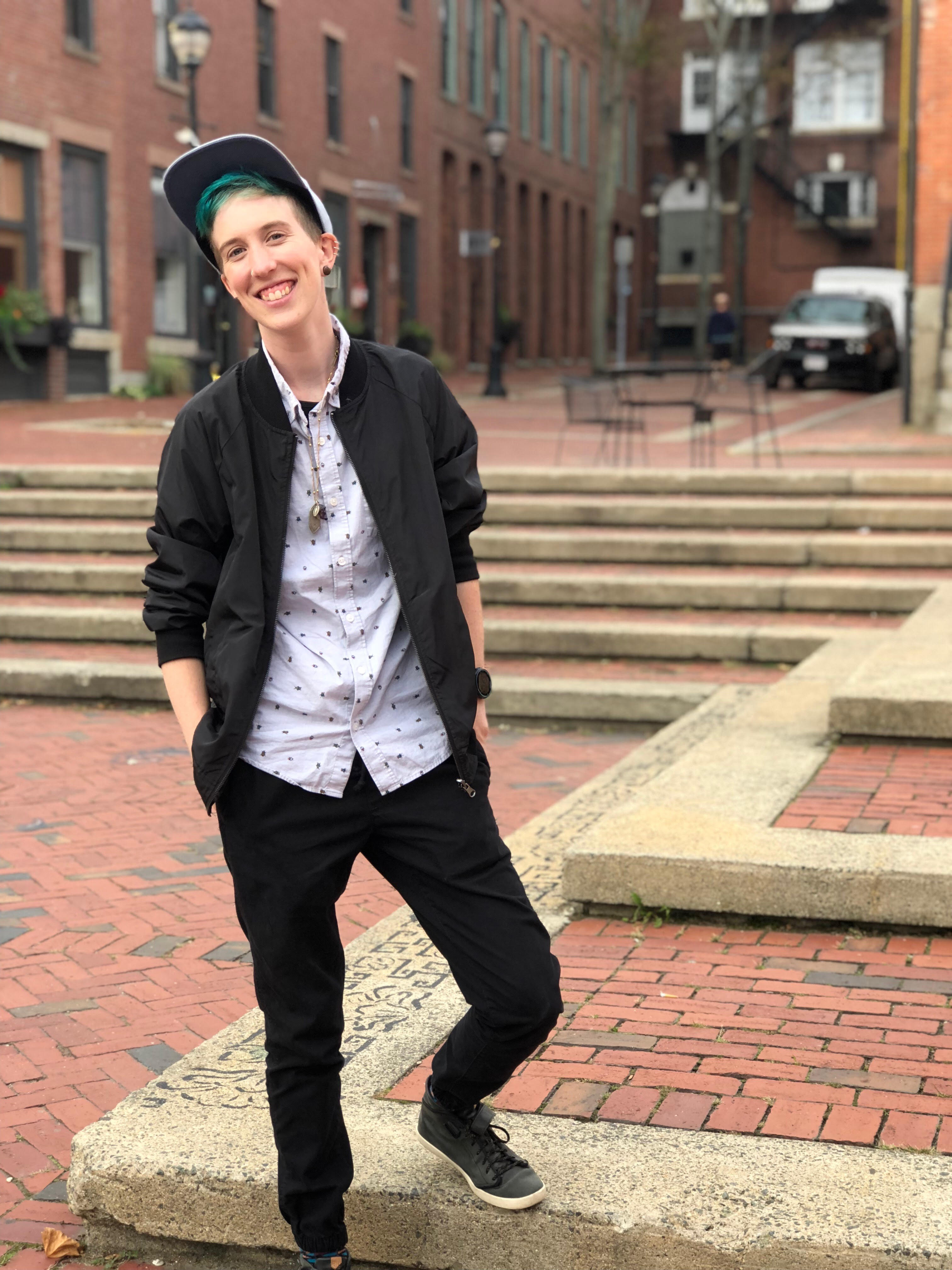 Lee,a human with blue hair, black pants, black jacket, white button up shirt, black shoes, and a snapback hat stands on a brick pathway